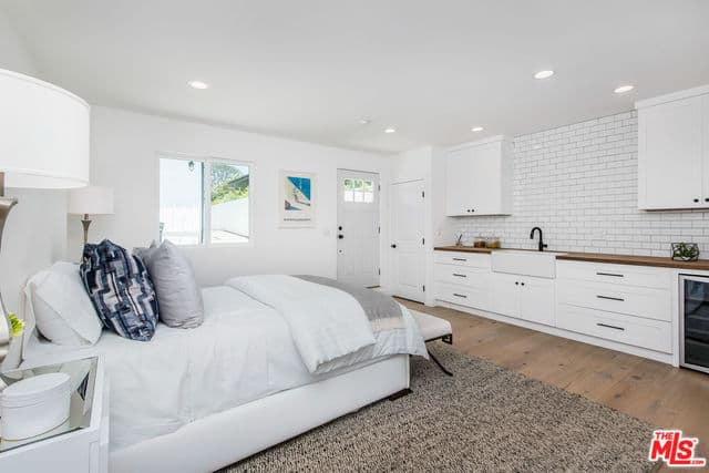 This bedroom has a peculiar design to its setup. The white bed with white sheets blends with the white walls and flanked by table lamps. Across from it is a kitchen peninsula with a faucet and sink with a backsplash of white tiles arranged in a brick wall pattern.