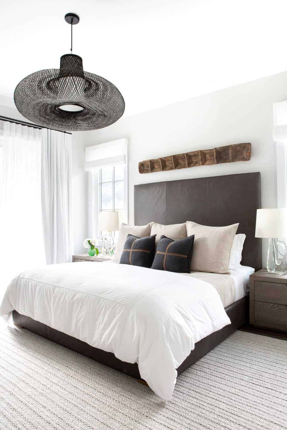 The light gray carpeted flooring complements the dark gray cushioned bed with a large cushioned headboard of the same hue. This is adorned with a wooden artwork mounted on the white wall above the headboard that matches with the decorative hood of the pendant light.