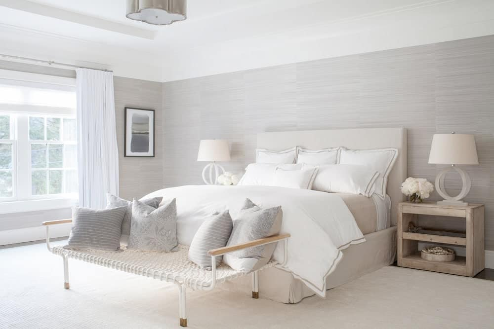 This chic and bright Farmhouse-style bedroom has a beige cushioned bed flanked with wooden bedside tables bearing table lamps with matching beige hoods. This is complemented by the light gray walls and white tray ceiling brightened by the window.