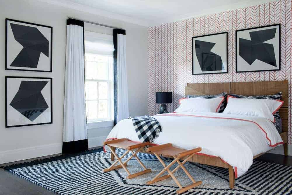 The rustic wooden traditional bed that has a wooden headboard is matched well with the two wooden foldable chairs at the foot of the bed. This is over a patterned area rug that adds a certain complexity to the room together with the red wallpaper.