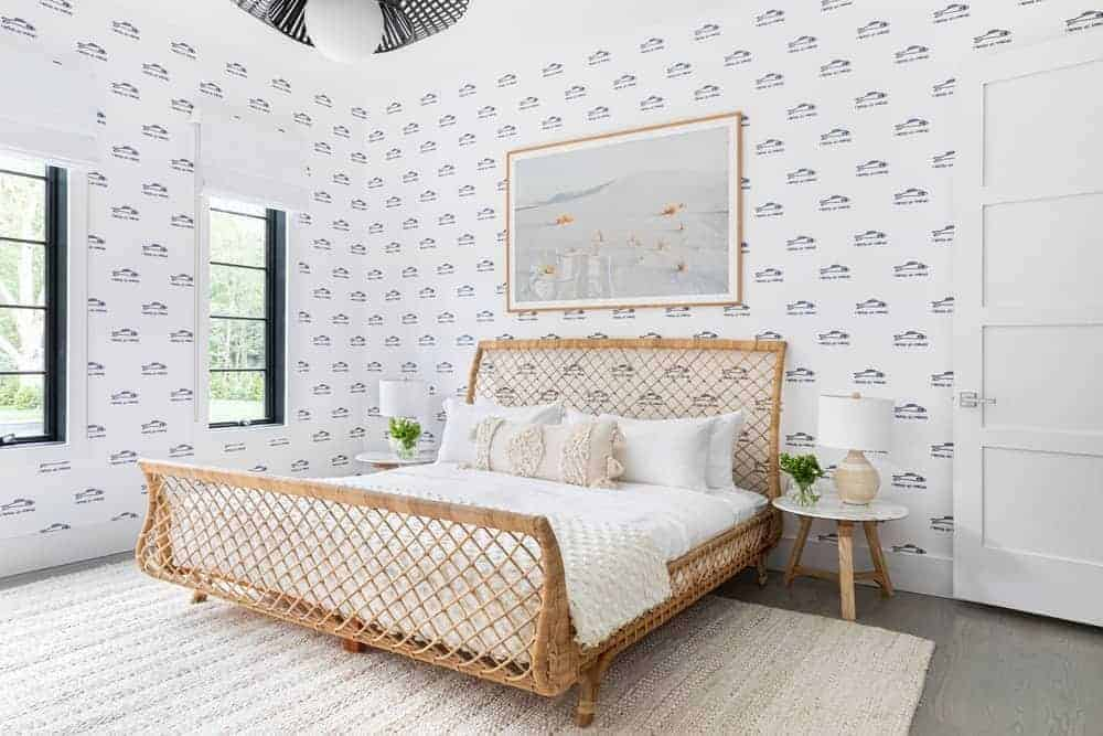 This Farmhouse-style bedroom has a large sleigh bed made of woven rattan from the foot all the way to the headboard. This works well with the white sheets of the bed and the white walls that have patterns on it.