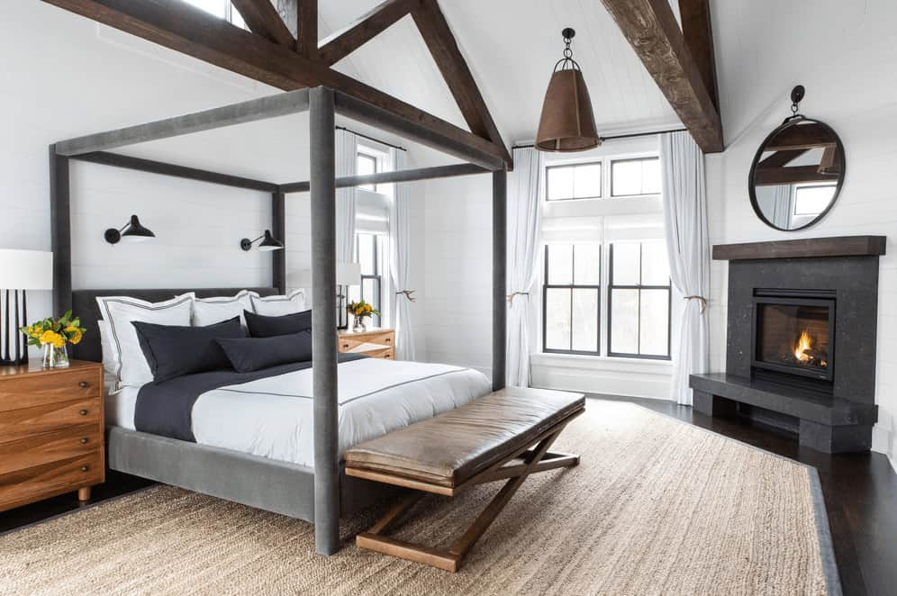 This Farmhouse-style bedroom has a gray four-poster bed that matches the fireplace in the corner with a dark gray mantle that stands out against the white walls. This is also contrasted by the large wooden beams of the white cathedral ceiling.