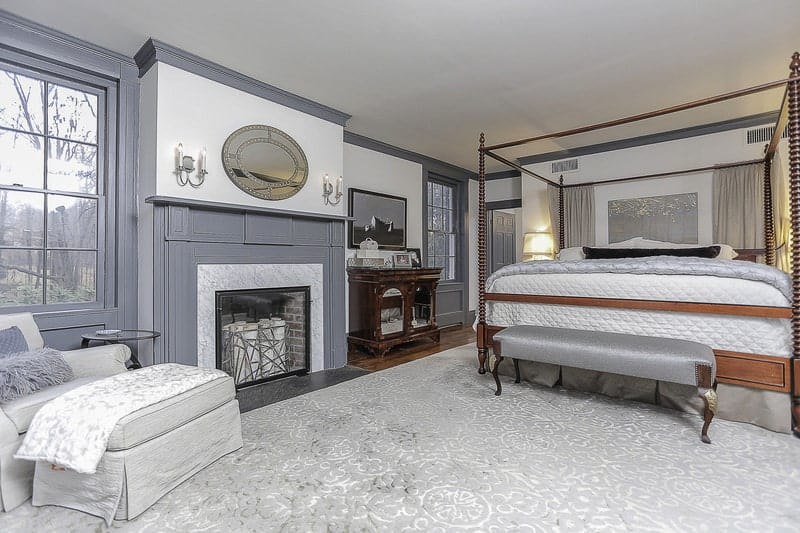 The large wooden four-poster bed dominates this bedroom. It has gray sheets that match the gray finish of the wooden walls and the mantle of the fireplace beside the sitting area that has a light gray cushioned armchair and a foot stool by the window.
