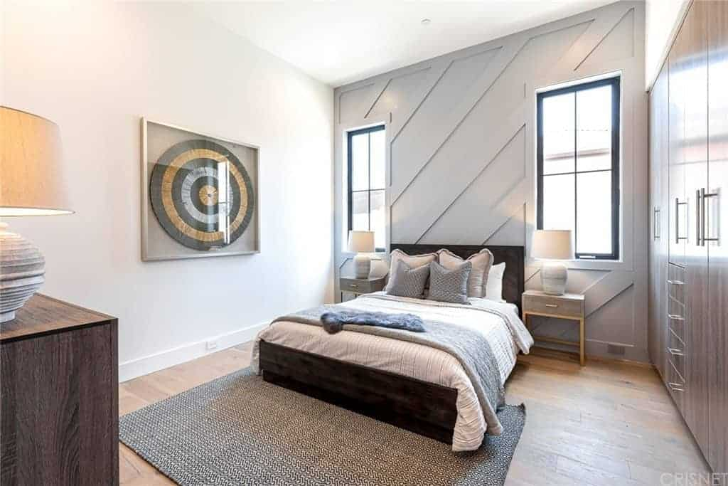 The far wall has a light gray hue and a Farmhouse-style wooden finish to it that pairs well with the dark wooden bed and the hardwood flooring. This bed has a headboard flanked by table lamps on bedside drawers as well as brilliant windows that brighten the white ceiling.