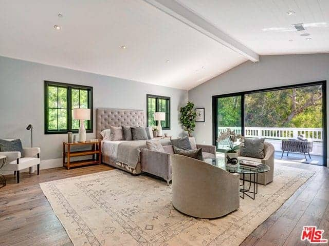 This wide and spacious primary bedroom has a large wall of glass that opens up to a bright balcony. This brings in an ample supply of natural lights to the white cathedral ceiling with an exposed wooden beam and the hardwood flooring that is covered with a beige patterned area rug.