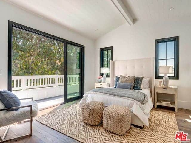 The highlight of this Farmhouse-style bedroom is the rustic woven patterned are rug that covers the hardwood flooring. It matches with the couple of ottomans at the foot of the bed with white sheets and a light beige cushioned headboard.