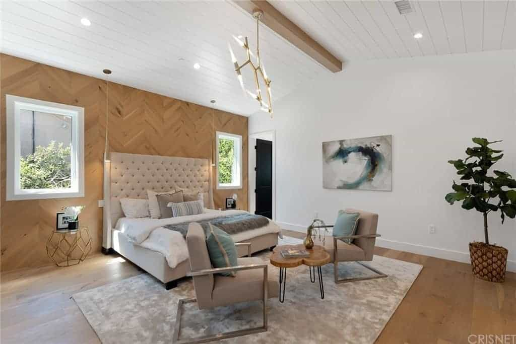 This is a Farmhouse-style bedroom through and through. It has a hardwood flooring that blends with the wooden wall behind the large tufted cushioned headboard. It also matches with the exposed wooden beam running the middle of the white cathedral ceiling that has a wooden plank finish.
