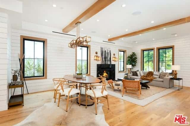 This Farmhouse-style dining area is beside the living room area both under the same white ceiling with exposed wooden beams supporting a modern decorative lighting over the elliptical wooden table paired with wooden wishbone chairs with furry cushions.