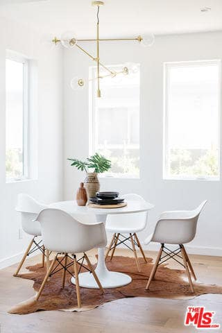 The white modern dining table has a circular shape to it that matches with the curves of the white modern dining chairs. This set stands out against the animal fur area rug over the hardwood flooring that balances the brightness of the walls and ceiling.