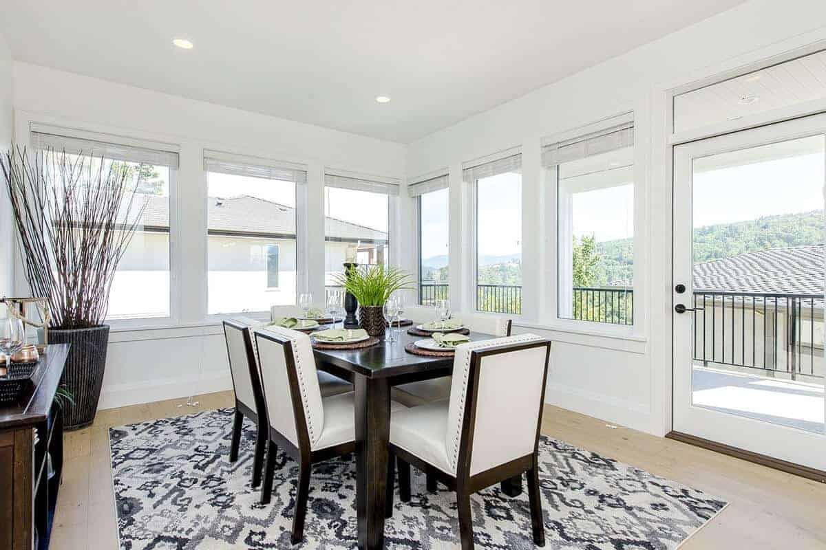 The white brightness of this Farmhouse-style dining room is due to the surrounding glass windows and glass door that bring in natural lighting to the white ceiling with recessed lights and the white walls that match the white leather upholstery of the chairs.