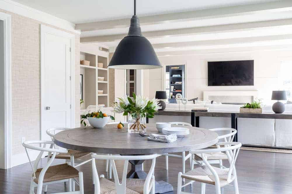 The round wooden dining table blends with the dark hardwood flooring that contrasts the white wooden wishbone chairs with woven wicker seats. This charming aesthetic is capped off with a farmhouse-style dome pendant light hanging from the white ceiling.