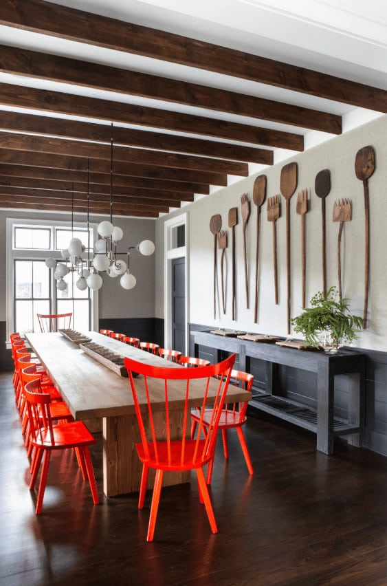 This dining room has a white ceiling dominated by the exposed wooden beams that match the hardwood flooring and the large rectangular wooden dining table surrounded by brilliant red orange wooden chairs and topped with a peculiar modern chandelier.