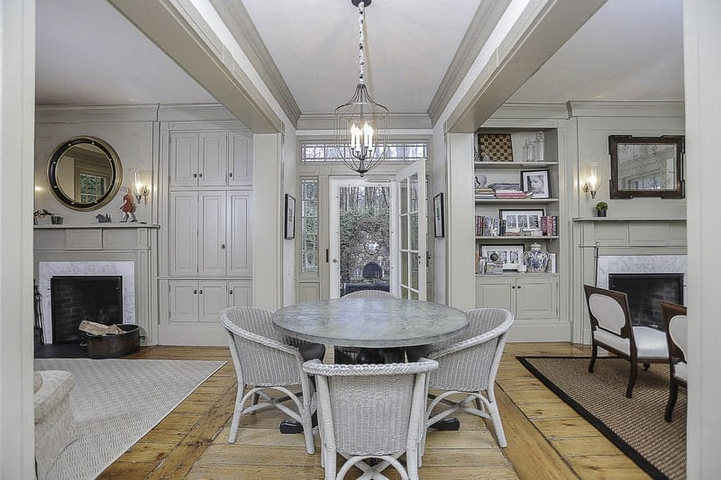 The rustic woven wicker dining chairs are painted with a light gray hue that matches with the gray surface of the round dining table with dark wooden legs that stand out against the hardwood flooring. This dining set also matches with the light gray ceiling and walls.