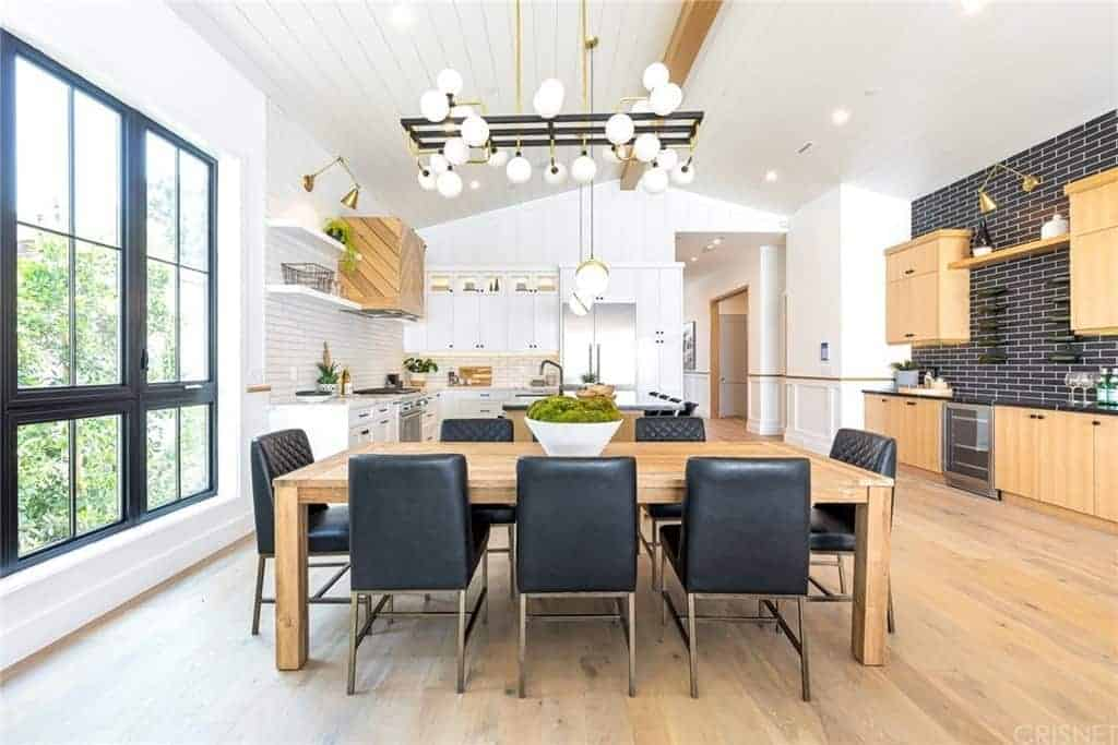 The black leather cushions of the modern dining chairs matches with the black frames of the large window, the black brick backsplash of the kitchen and the black metal frames of the modern lighting above the simple wooden dining table.