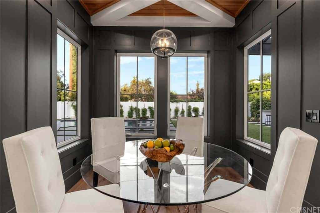 This informal dining area is inside a small nook alcove of dark gray walls with windows that bring in natural lighting for the round glass-top table and its white cushioned chairs that pairs well with the white exposed beams of the wooden ceiling.