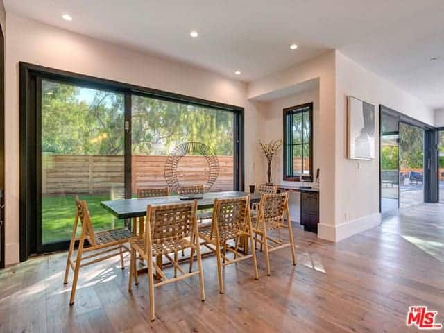 This simple dining room has a beautiful lush green background of the landscaping outside with a brown wooden fence. This scenery complements the rustic wooden dining chairs that have woven backs and seats matching with the hardwood flooring.