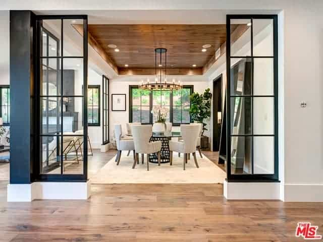 This is an elegant Farmhouse-style dining room with a charming wooden tray ceiling that supports a round Farmhouse-style chandelier complementing the round glass-top dining table surrounded by cushioned wing-back chairs.