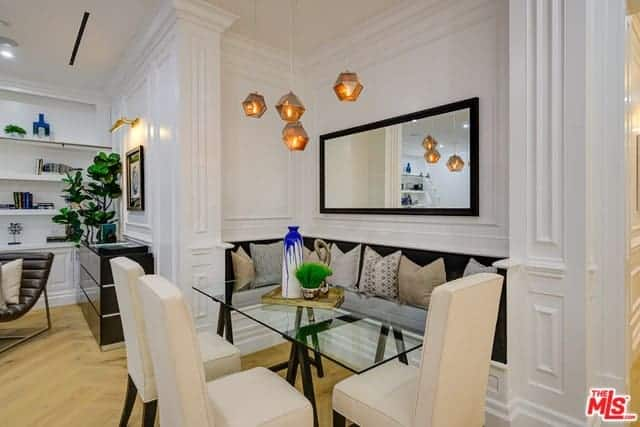 This is an informal dining area by the living room area. This is embedded into a tiny alcove of the white wall that has a built-in bench with black cushions paired with a rectangular glass-top dining table and beige cushioned chairs with black wooden legs.