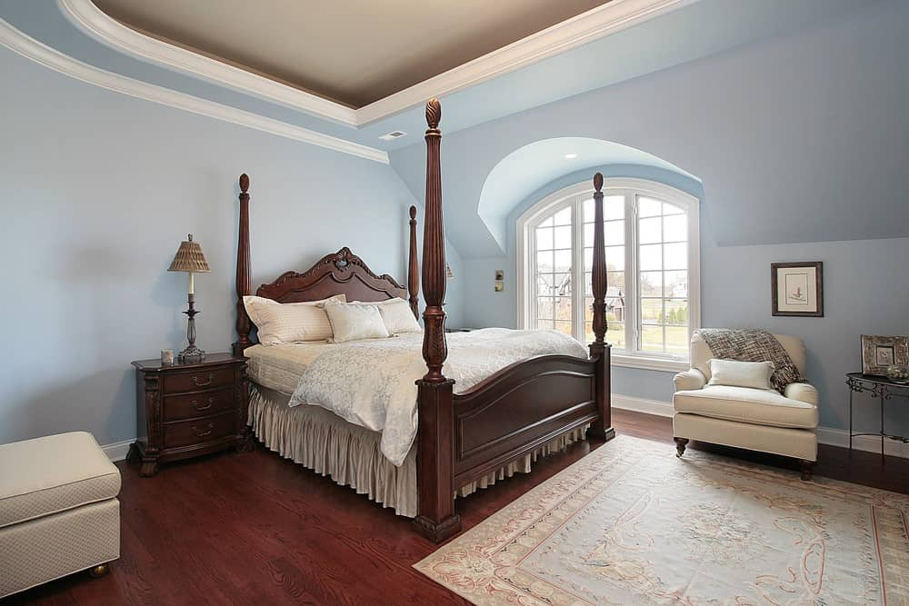 Large primary bedroom with a classy tray ceiling along with hardwood flooring while sky blue walls surrounding the room. The bedroom has a large classy bed setup.