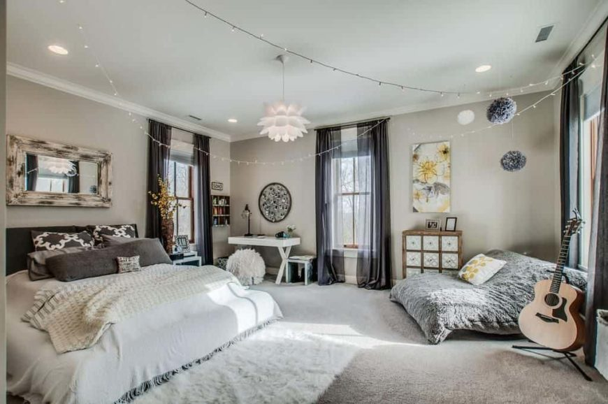 Large primary bedroom with gray walls and gray carpet flooring. There's a large comfy bed and a nice lounging couch on the side, along with a small study desk in the corner.