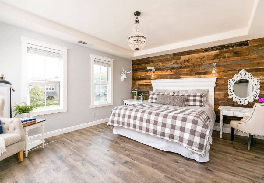 Large primary bedroom with gray walls and a stylish rustic wall behind the bed. The room also features hardwood flooring and a tray ceiling.