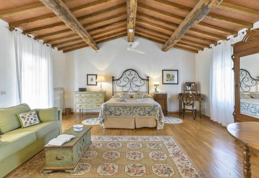 Spacious primary bedroom featuring a wooden ceiling with exposed beams along with hardwood flooring. The room offers a classy bed along with an olive green couch on the side.