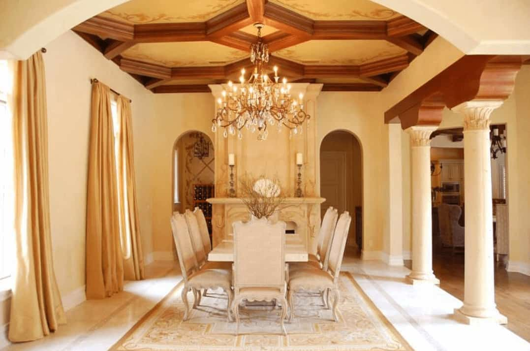The formal dining room has beige walls, beige ceiling, beige fireplace and beige dining set. These are complemented by the wooden exposed beams of the ceiling that hangs a majestic chandelier over the rectangular dining table.