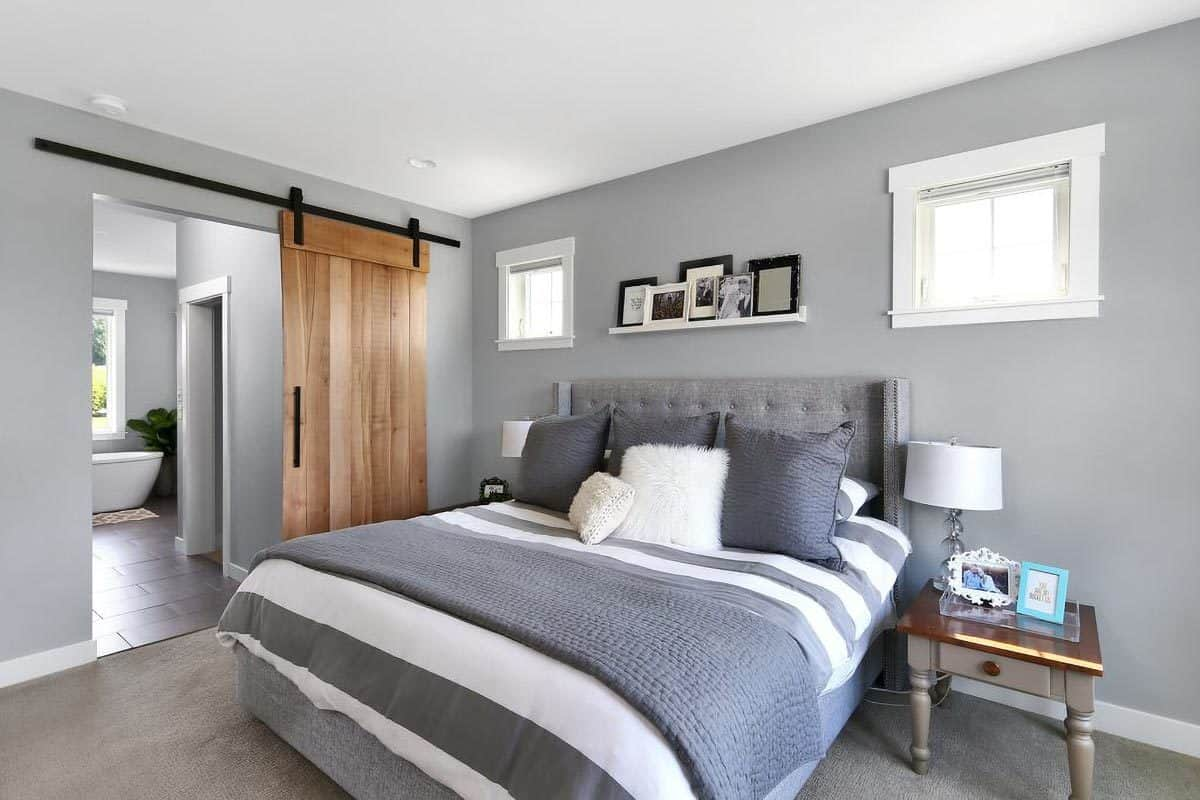This lovely bedroom has a crisp and clean vibe to its gray sheets, gray pillows, walls and flooring. These are then complemented by a rustic wooden sliding door supported by wrought iron giving the room additional character.