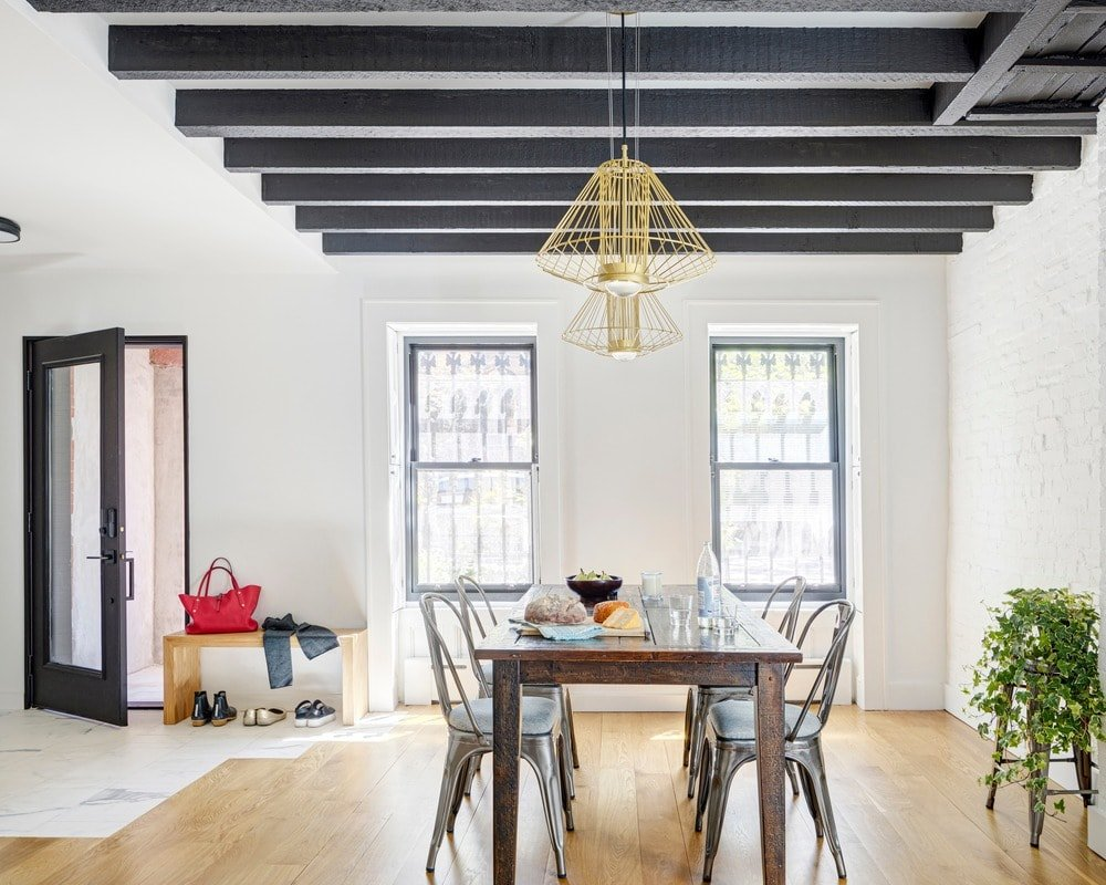 This Industrial-style dining room has modern metal dining chairs paired with a dark wooden dining table that complements the exposed wooden beams of the white ceiling. This is augmented by the golden decorative pendant lights.