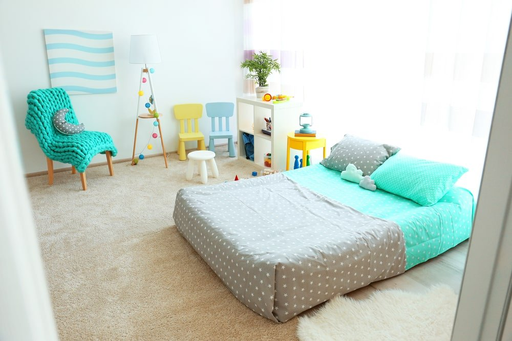 The brilliant green elements of this kid's bedroom are brightened further by the natural lights filtered through the sheer curtain of the window behind the bed and the small wooden white shelf beside it for toy storage. These bright elements are balanced by the colorful minute details scattered in the room.