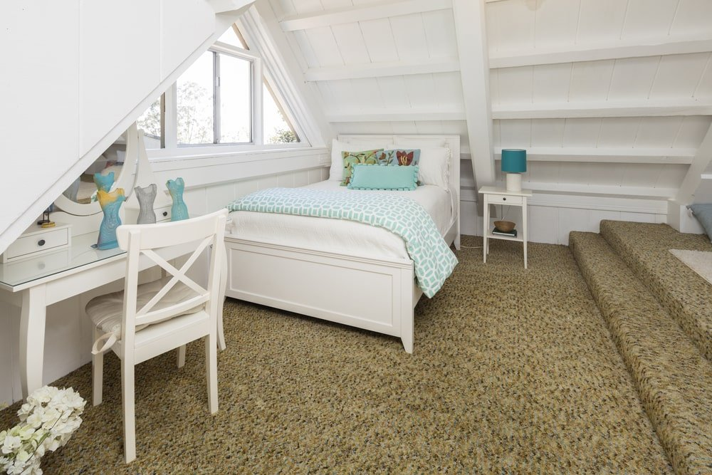 This is a beautiful kid's bedroom located at the attic of the house. It offers a unique aesthetic that has a low white cathedral wooden ceiling that enables a triangular window by the matching white bed and desk. This stands out against the brown carpeted flooring.