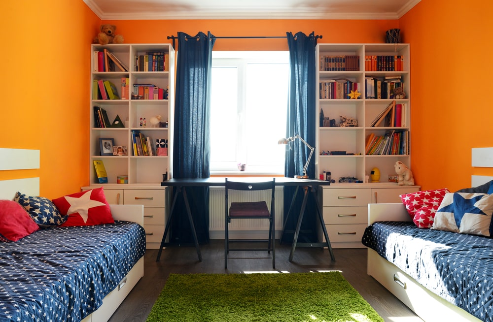 The bright orange walls of this kid's sharing bedroom sets a cheerful tone for the two white beds that match with the white bookshelves flanking the desk by the window. This brings in an abundance of natural lighting that brightens the white ceiling and green area rug.
