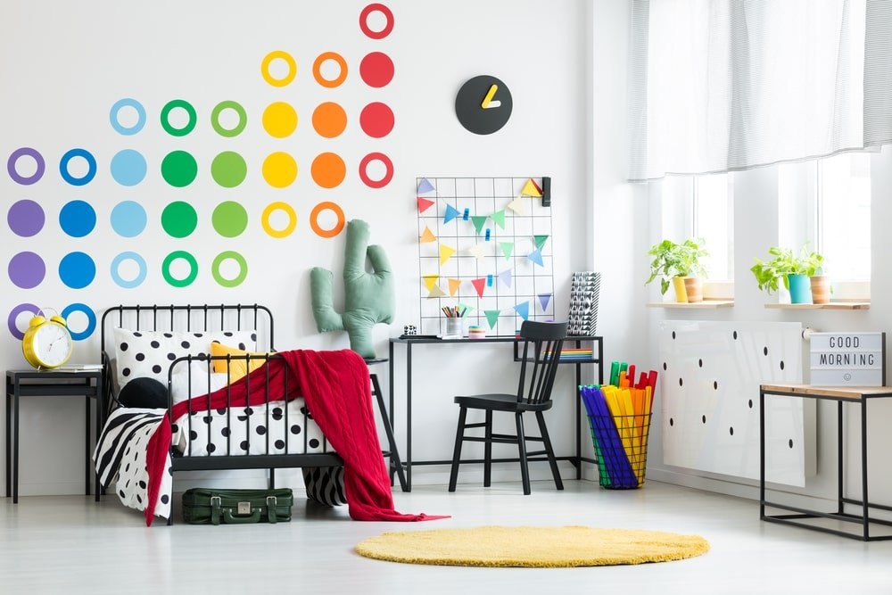 Gender-neutral kids' bedroom with white walls and colorful accessories.