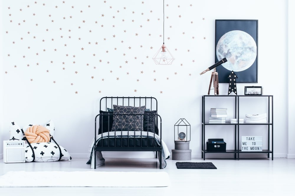 The white walls of this bright bedroom are filled with small stars to create a beautiful starry aesthetic for the kid who adores astronomy. There is even a small telescope on the bookshelf beside the bed as well as a poster of the full moon that stands out against the white wall.