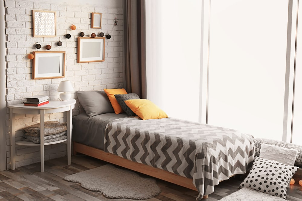 The gray patterned sheets of the small bed matches well with the gray brick wall and the gray tone of the hardwood flooring that is topped with a gray area rug near the white bedside table. These gray elements are brightened by the wide window and complemented by the minute orange details.
