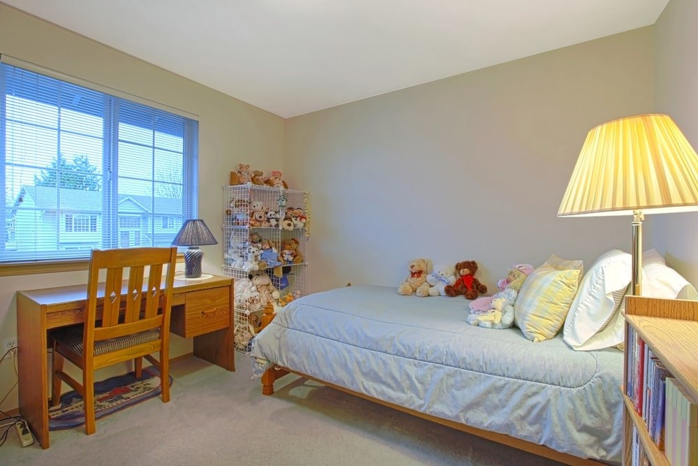 This charming and homey kid's bedroom has a large wire mesh shelf for storage of stuffed toys. This is placed by the foot of the wooden bed with light-hued sheets and pillows. This wooden bed frame matches with the study desk and chair by the window.