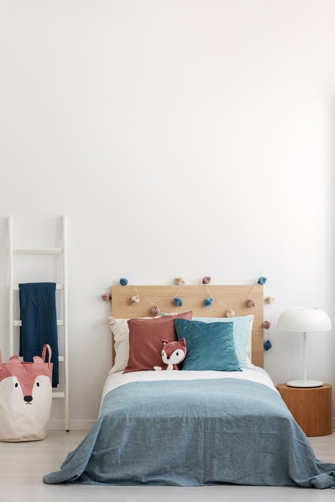 This is a simple and small kid's bedroom with a small platform bed that has a wooden headboard adorned with colorful decors and pillows as well as a stuffed fox. This matches with the bin beside the bed that could either be used for laundry or toy storage.