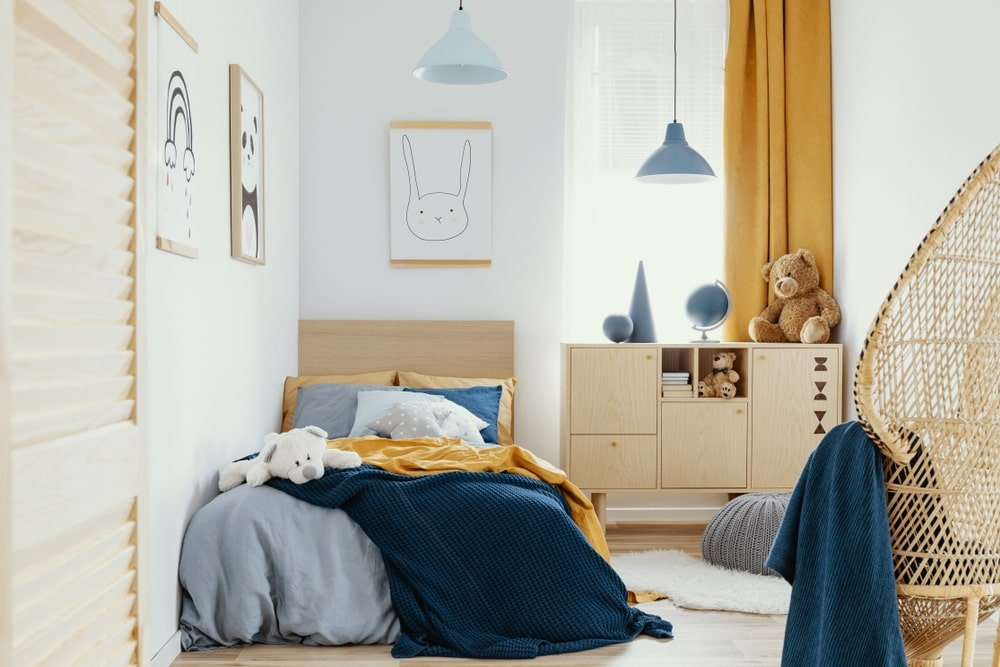 This is a simple kid's bedroom with a platform bed that has a bare wooden headboard complementing the white wall. This headboard matches well with the cabinet beside it that is adorned with decors and stuffed toys. They also match with the hardwood flooring and the woven wicker chair at the corner.