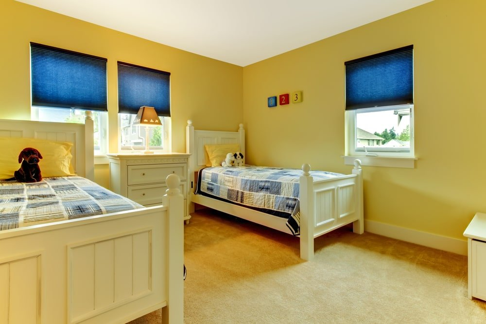 This is a sunny and cheerful kid's sharing bedroom with two yellow wooden beds to fit in with the mustard yellow walls and beige carpeted flooring. These beds also match with the dresser in the middle beneath the window bearing a yellow lamp.