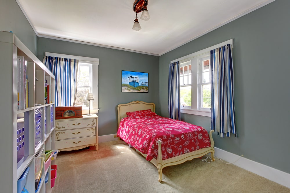 The red patterned sheet of the beige sleigh bed stands out in this kid's bedroom surrounded by gray walls, white ceiling and beige carpeted flooring. This bed is a match for the elegant dresser on the side by the window that has the same blue striped curtains as the res of the windows.