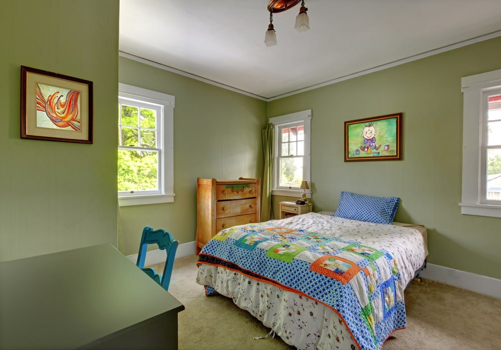 The relaxing avocado green walls of this kid's bedroom are adorned with various colorful artworks framed with wood to match the small semi-flush light at the white ceiling. The light hues of the bed sheets and pillow is a nice pairing for the walls and the beige carpeted flooring.