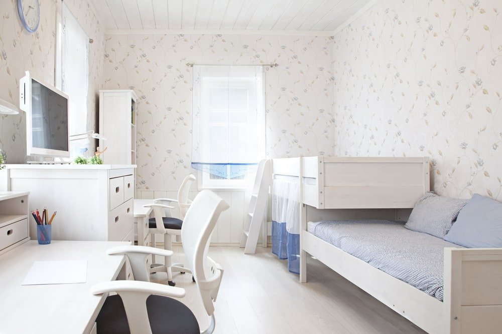 The brightness of this kid's bedroom is mostly due to the abundance of natural lights coming in from the windows that brighten the white patterned wallpaper that has minute details. These windows also brighten the white wooden structures of the bunk bed, dresser and desks.
