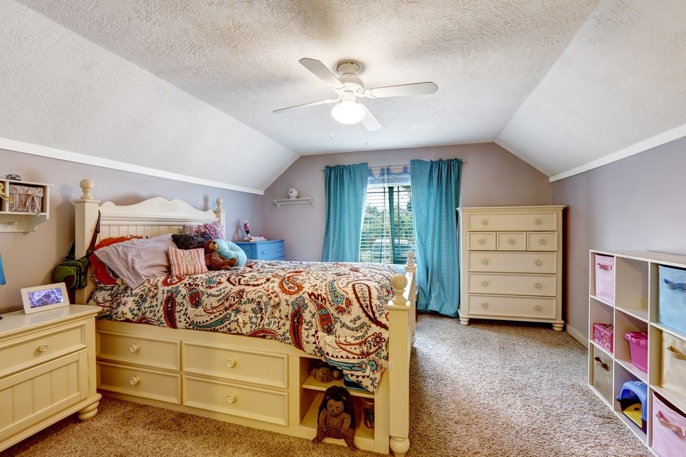This spacious kid's bedroom has a gray cove ceiling that blends well with the gray walls brightened by the window on the far side. This gray tone works well to complement the yellow wooden bed and its bedside drawer as well as the large wooden dresser beside the window.