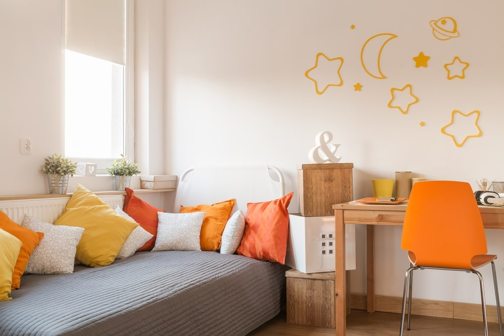 This kid's bedroom has playful orange details that give life and a quirky side to the neutral elements of the wooden desk and hardwood flooring. This also gives a dash of color to the plain white wall and the gray sheet of the cottage bed.