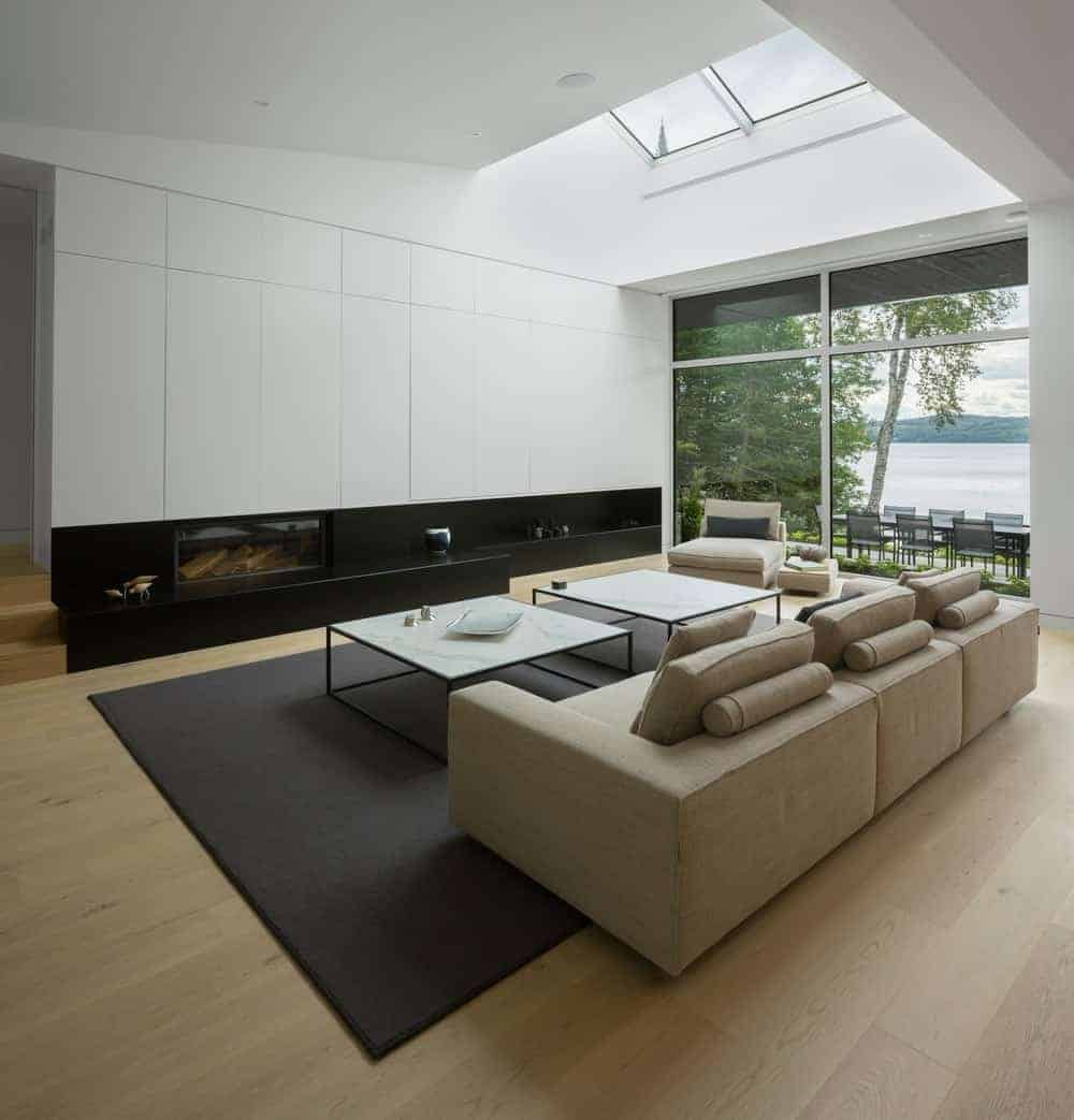 Modern living space with a cozy couch and a pair of center tables, set on a black area rug and has a fireplace.