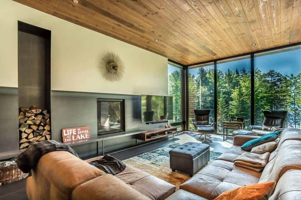Contemporary living room boasting a large brown sofa set and a pair of modern seats together with a large flat-screen TV on the wall. The room boasts a wooden ceiling and floor-to-ceiling glass walls and windows overlooking the stunning outdoor view.