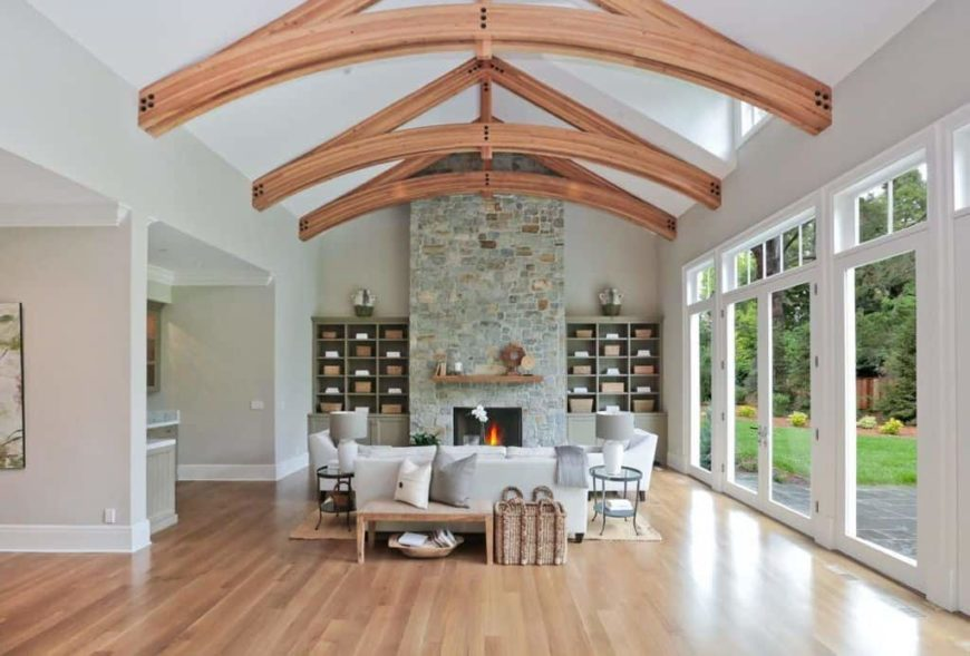 A spacious formal living room boasting a tall vaulted ceiling with large exposed beams along with hardwood flooring and a stone fireplace with built-in shelving on both sides. The area offers classy white seats.
