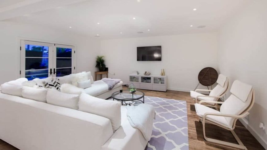 Large living space featuring white walls and a white ceiling lighted by recessed ceiling lights. The room offers a large white L-shape sofa set and two reclining chairs on the side, along with a TV on the wall.