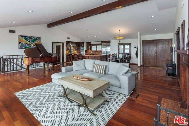 A spacious living space with hardwood flooring and a white ceiling. There's an L-shape sofa set along with a stylish center table near the fireplace. There's a classy grand piano near the staircase too.