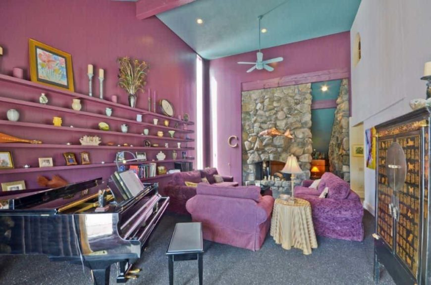 This living room features a purple color scheme, along with a stone fireplace and a black piano. The room also has gray carpet flooring and a tall ceiling.